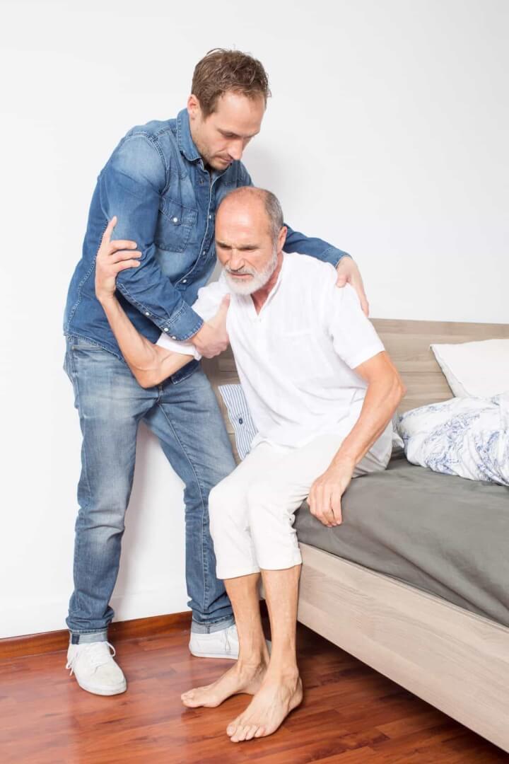 Krankenpfleger hilft Mann beim Aufstehen