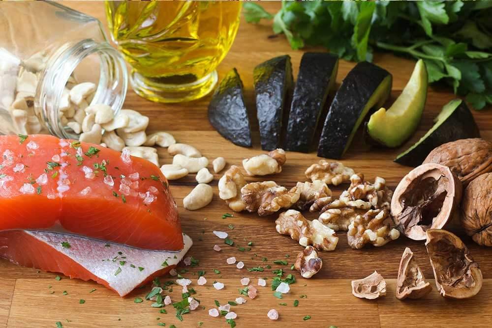 Alimentos ricos en Omega 3 como las nueces, salmón y aguacate, entre otros, en una mesa.