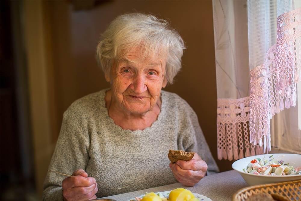Anciana sentada en una mesa comiendo alimentos saludables.