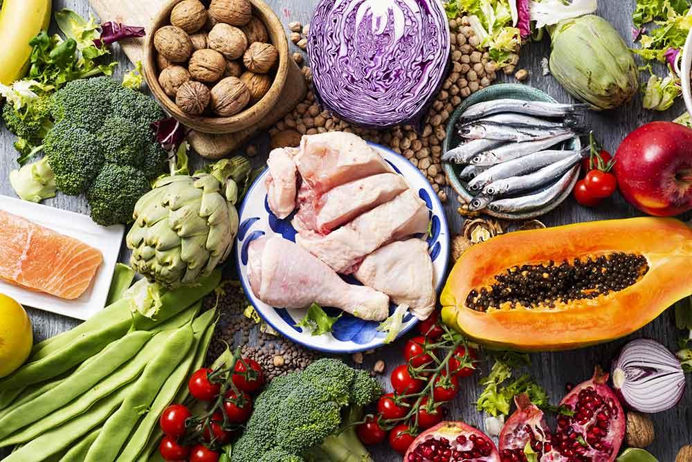 Alimentos ricos en fibra como verduras y frutas, así como muslos de pollo en el centro de una mesa.