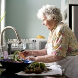 woman-preparing-a-meal-in-kitchen-725x483