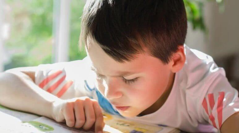 Niño con autismo leyendo un libro.