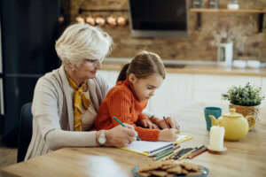 Abuela y niña coloreando un cuaderno