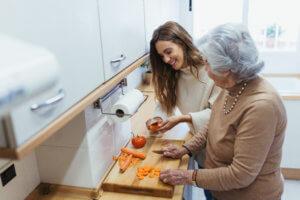 cuidadora y anciana cocinando
