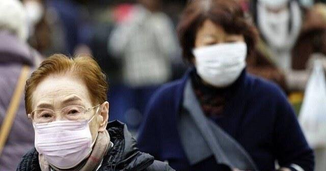 Dos mujeres asiáticas caminando por la calle ataviadas con una mascarilla.