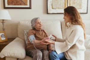 cuidadora midiendo la tensión a la abuela