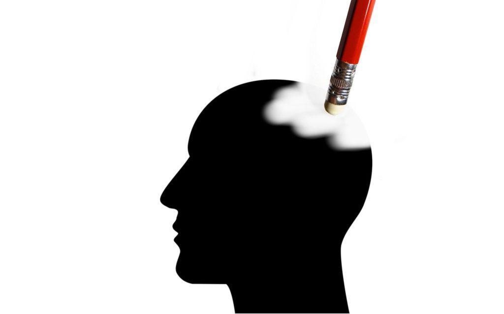 Foto de una goma de borrar borrando parte de la cabeza de la silueta de una persona.