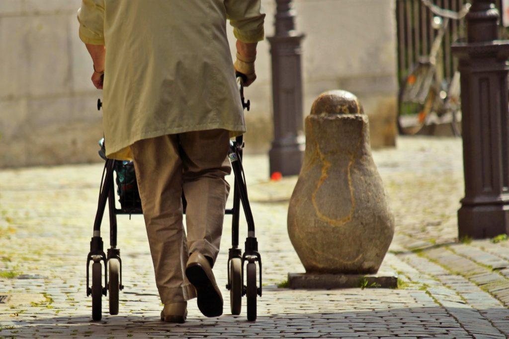 Persona mayor se apoya para caminar en un andador con ruedas.