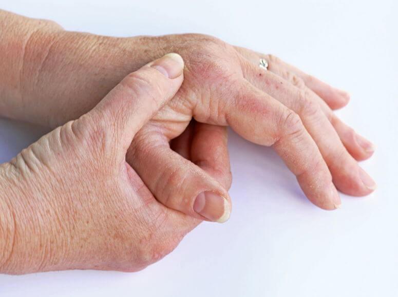 Dos manos de persona mayor frotándose una a la otra.