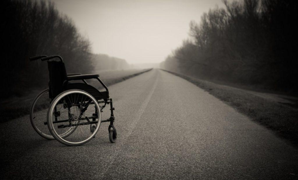 Silla de ruedas en medio de una carretera abandonada.