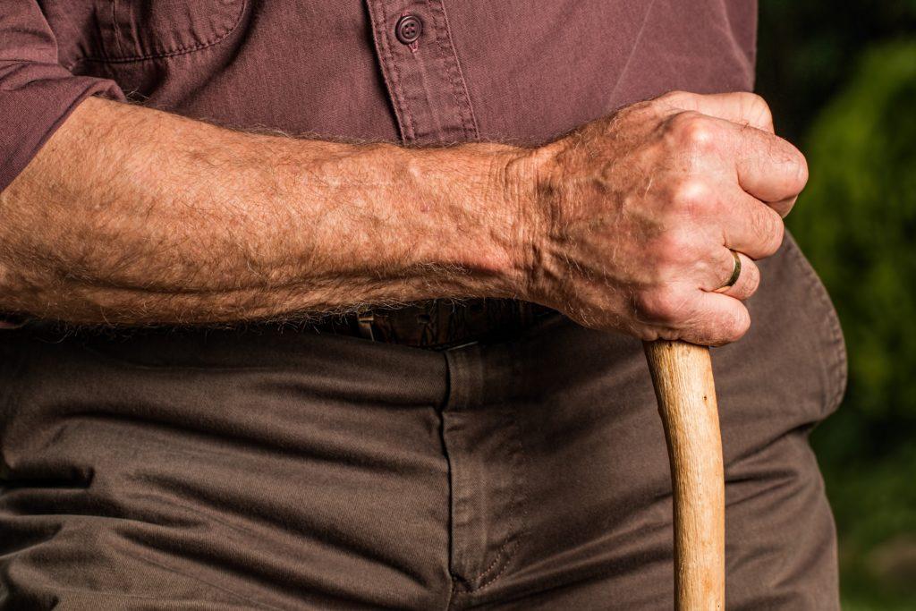 Primer plano de la piel del brazo de un anciano apoyado en un bastón.