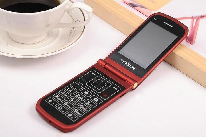 Teléfono Artfone de color rojo con la tapa desplegada rodeado de una taza de café.