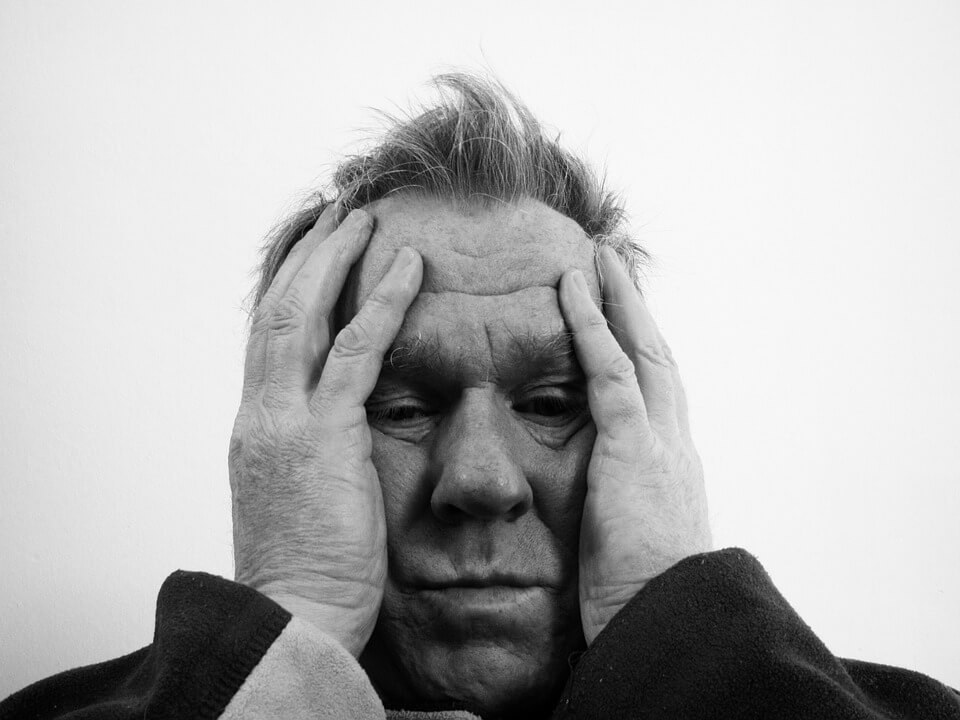 Hombre mayor echándose las manos a la cabeza por dolor