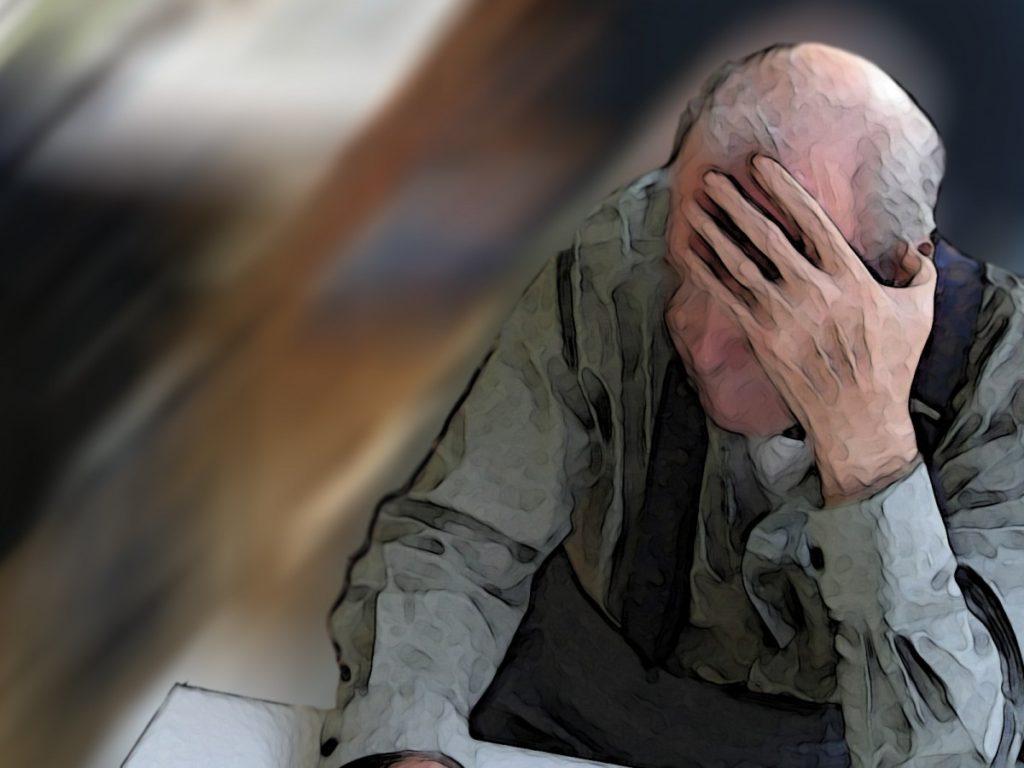 Persona mayor con la cabeza agachada y echándose la mano a la cabeza.