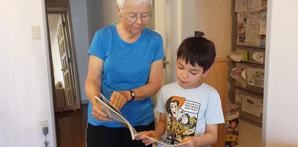 Niño mostrándole a su abuela un libro de frases bonitas para ella.
