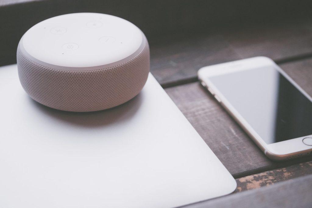 Altavoz inteligente funcionando junto a un portátil y un teléfono movil.