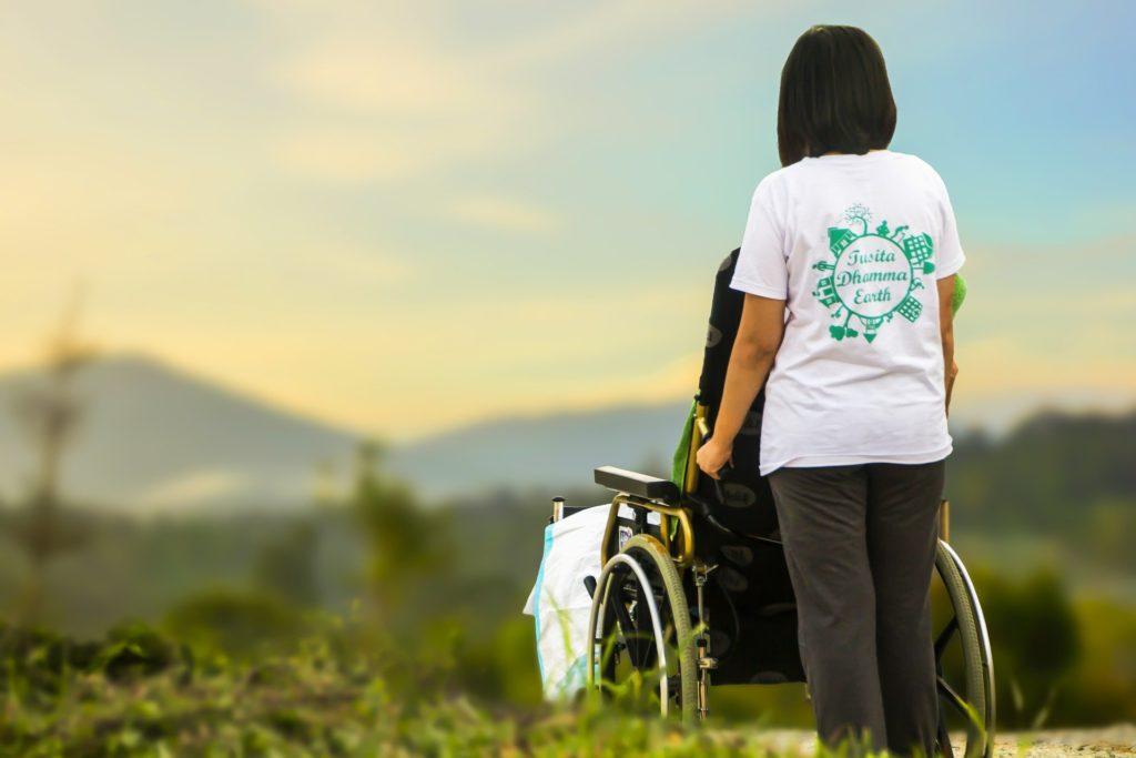 Enfermera cuidadora de mayores paseando una persona mayor en una silla de ruedas.