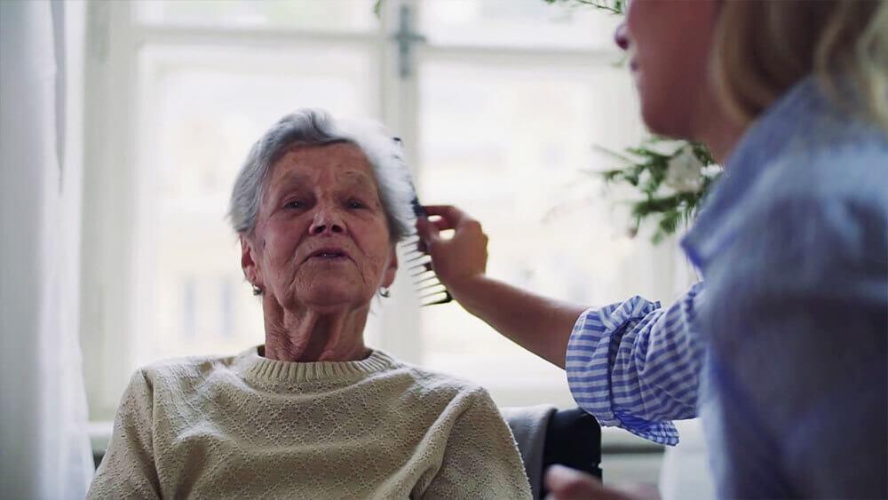 Cuidadora a domicilio peinando a mujer mayor.