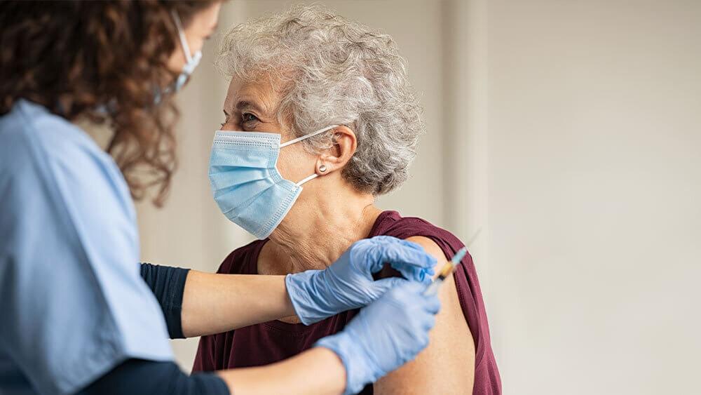 Enfermera a domicilio poniéndole una inyección a una abuela.