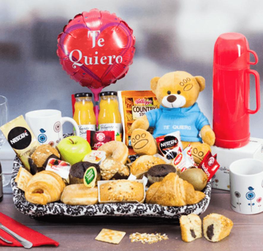 """Cesta regalo de desayuno con bolleria, zumos, café, taza, peluches y globo con """"te quiero""""."""