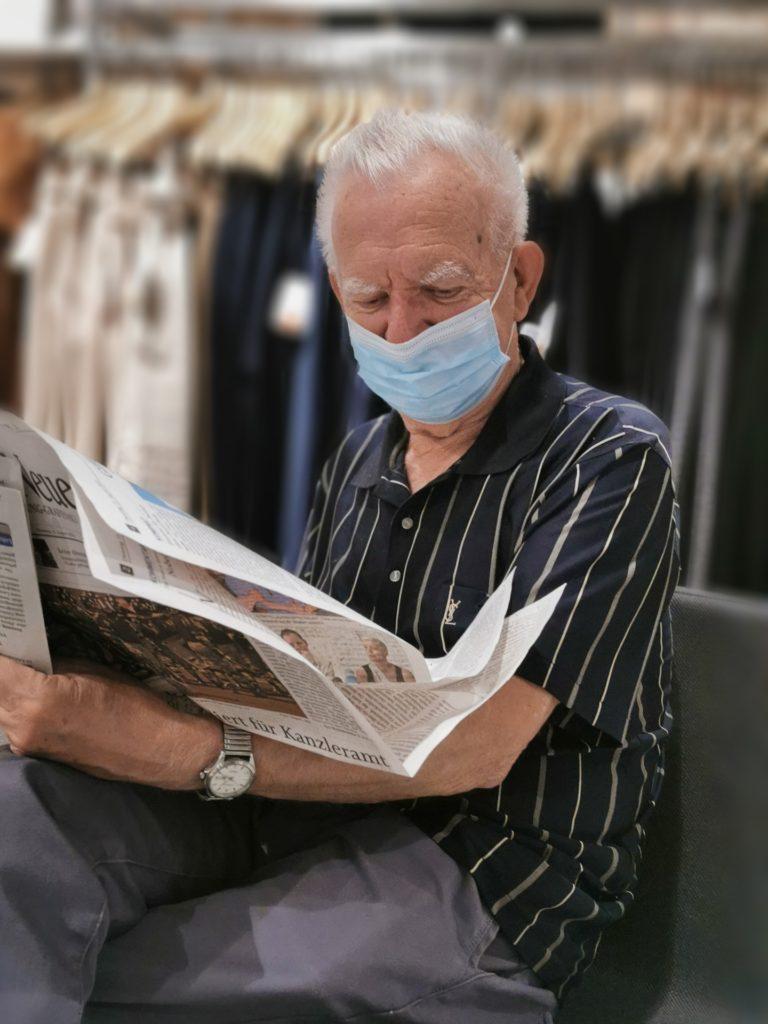 Persona mayor leyendo el periódico ataviado con una mascarilla.