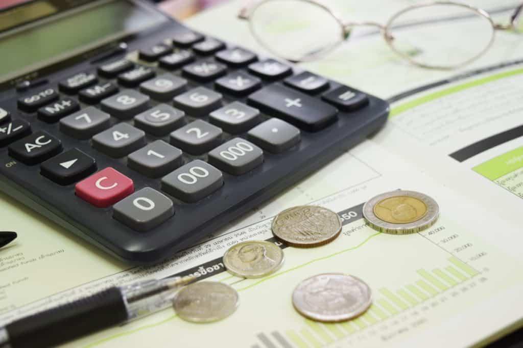 Calculadora de oficina rodeada de una pluma y monedas.