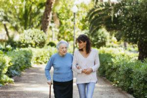 abuela con bastón caminando con la ayuda de una cuidadora