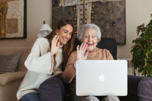 abuela y cuidadora hablando por videollamada