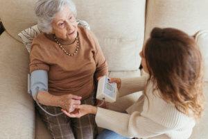Cuidadora midiéndole la tensión a la abuela