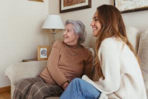Abuela y cuidadora riéndose en el sofá