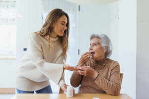 Abuela tomándose un medicamento para el resfriado