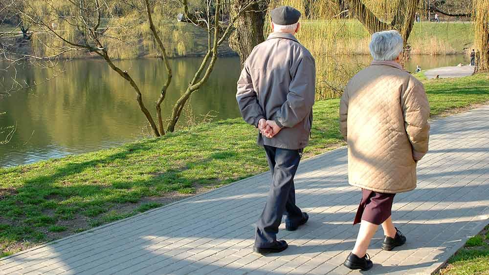 Pareja de ancianos caminando en una senda al lado de un río.