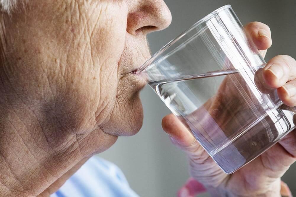 Anciano bebiendo agua.