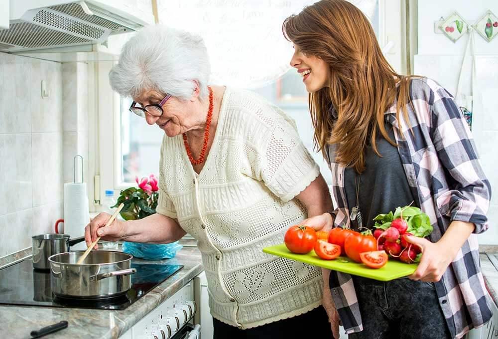 Mujer joven ayuda a abuelita de 80 años a cocinar su dieta equilibrada.