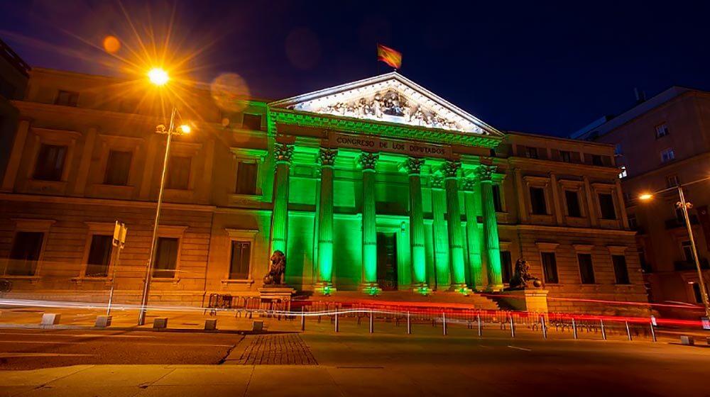 Fachada del Congreso de los Diputados de España iluminada de verde en el Día Mundial de las Enfermedades Raras.