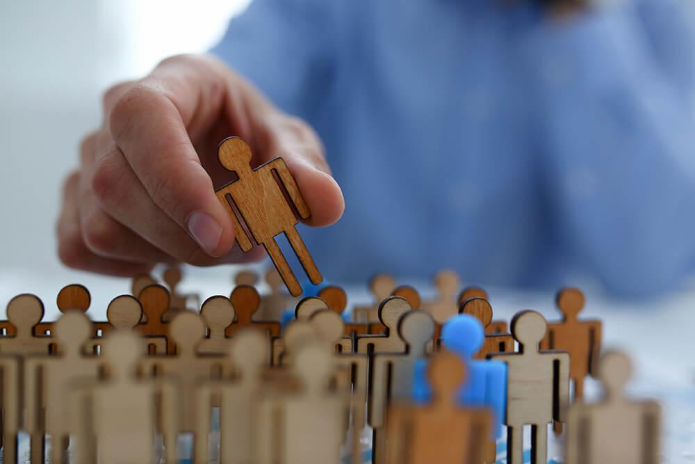 Un hombre coge una figura entre distintos muñecos de personas.
