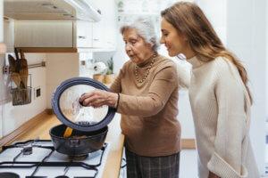 Abuela y cuidadora cocinando