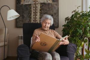 Abuela mirando un álbum en el salón