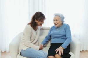 Abuela y cuidadora hablando en el sofá