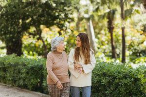 Abuela y cuidadora caminando por el parque