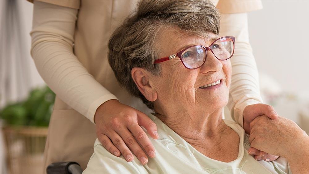 Anciana cogiendo de la mano a cuidadora experta en técnicas para mantener la paciencia en personas mayores.