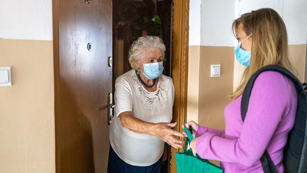 Nieta dando a su abuela, ambas con mascarilla, la compra en el umbral de su casa durante la pandemia