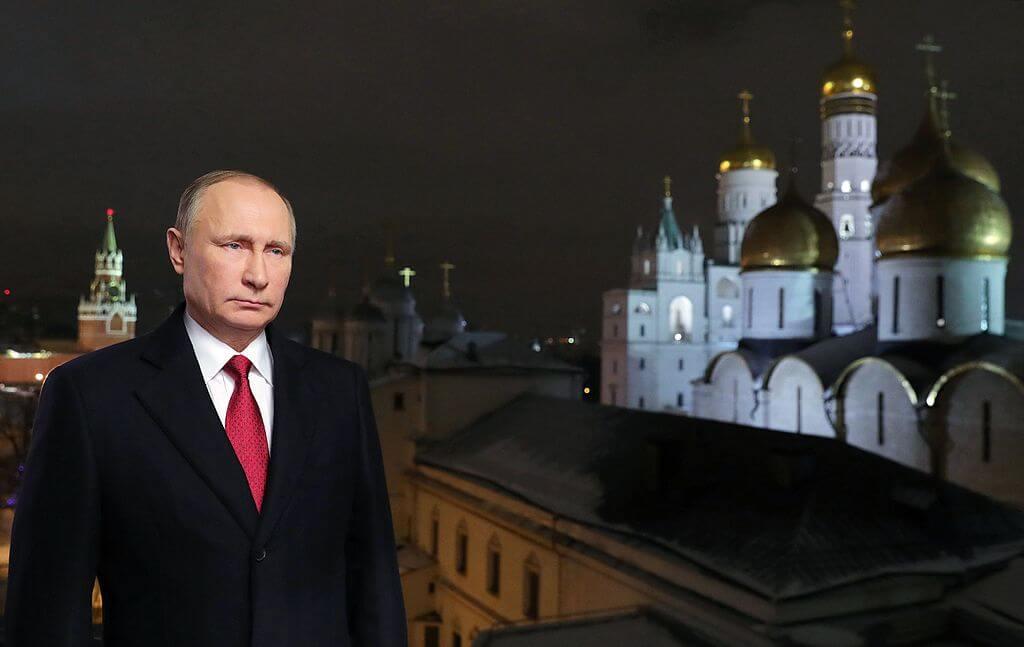Vladimir Putin posando en el discurso de nochebuena con el Kremlin al fondo