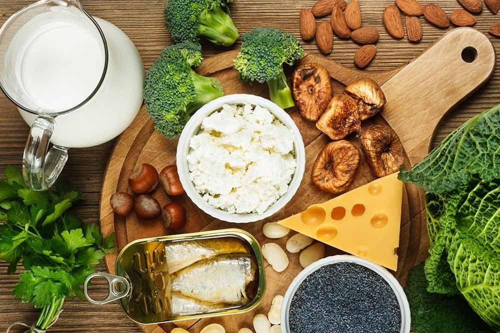 Distintos alimentos con calcio como la leche, el queso, sardinas, almendras y avellanas en una mesa.