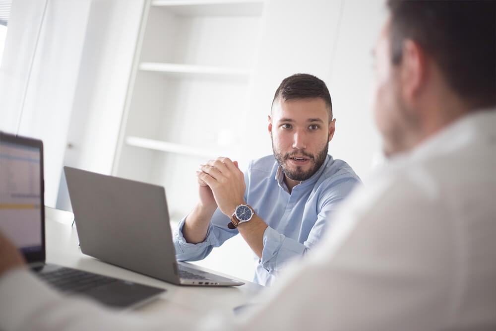 Daniel ibiza CEO de Aiudo sentado con otra persona de espaldas en una mesa.