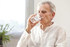 Anciano bebiendo un vaso de agua