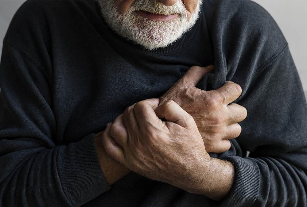 Adulto mayor se lleva la mano al corazón y tiene cara de preocupación.