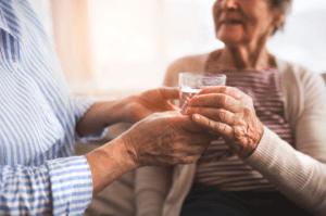 Anciano hidratando a una abuela con un vaso de agua