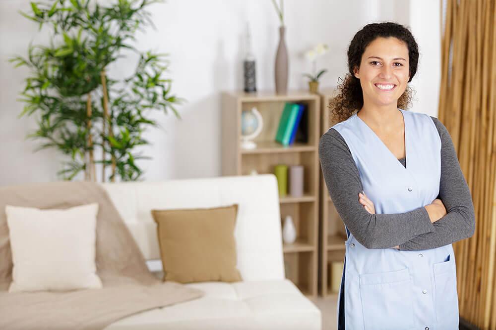 Trabajadora del hogar sonríe ante la cámara.