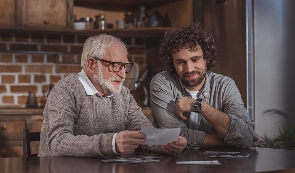 Padre lee unas frases del día del padre que su hijo le ha escrito, quien está a su lado.